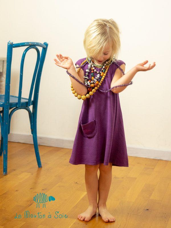 Une fillette en robe violette à poche
